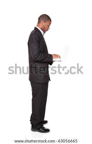 Isolated studio shot of an African American businessman standing and using a laptop computer. - stock photo