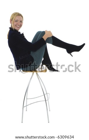 Isolated studio shot of an attractive young woman sitting on a high stool