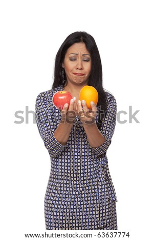 Isolated studio shot of an unhappy Latina woman examining an apple and orange, deciding what to eat for her healthy diet. - stock photo