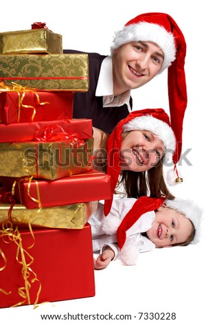 Isolated studio shot of happy young family of three wearing Santa's hats with a lot of Christmas presents.