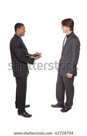 Isolated studio shot of two businessmen brainstorming and taking notes in a notebook. - stock photo