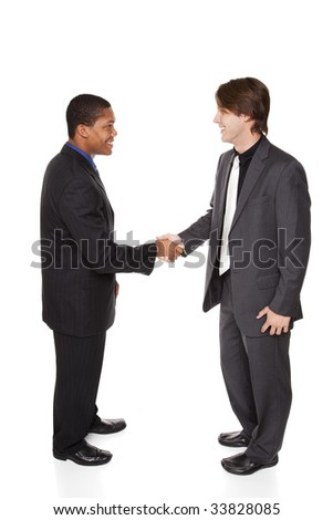 Isolated studio shot of two businessmen shaking hands in a warm, friendly greeting. - stock photo