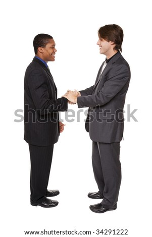 Isolated studio shot of two businessmen shaking hands in a warm, friendly greeting.