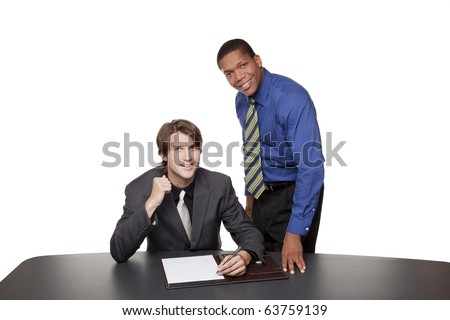 Isolated studio shot of two cheerful businessmen reviewing notes at a conference table and looking at the camera. - stock photo