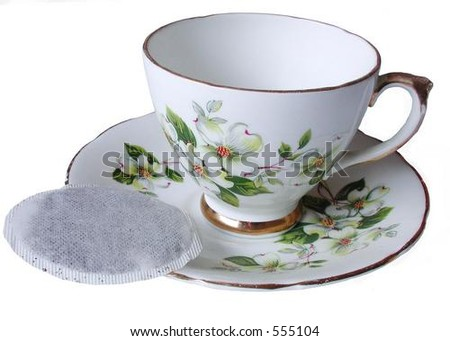 isolated tea cup and saucer with tea bag on side - stock photo
