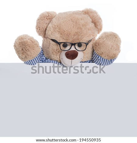 Isolated teddy bear holding an empty sign or placard for advertising. Concept for a message board for children. - stock photo