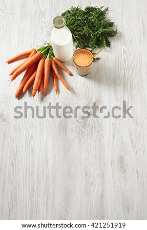 Isolated top view on wooden table, farm carrot harvest lying near bottle and glass filled with mix natural fresh juice and milk with golden drinking straw in it,for breakfast in cafe - stock photo