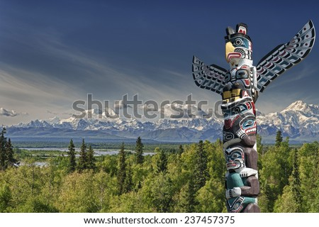 Isolated totem wood pole in mountain blue background - stock photo