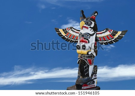 Isolated totem wood pole in the blue background - stock photo