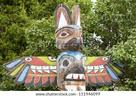 Isolated totem wood pole in the forest background - stock photo
