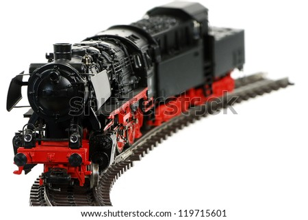 Isolated toy steam locomotive with a coal trailer - stock photo