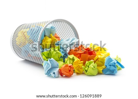 isolated tumbled office wastepaper basket with colourful crumbled paper ball - stock photo