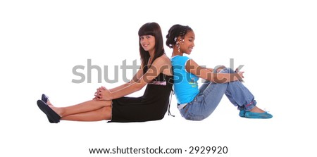 isolated two young girls sitting on the floor and leaning back to each other - stock photo