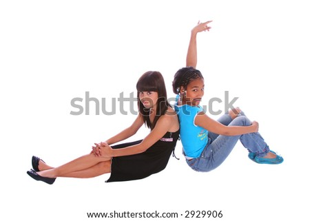 isolated two young girls sitting on the floor leaning back to each other. one girl raise her hand - stock photo