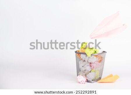 isolated wastebasket full of color waste paper and paper airplane - stock photo
