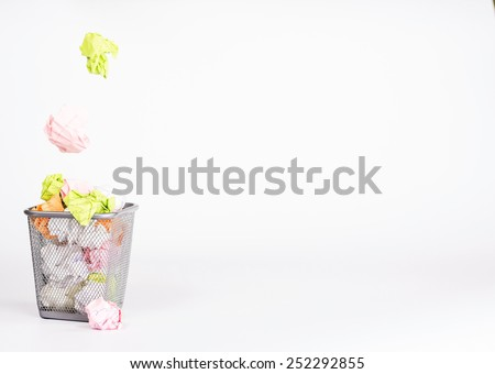 isolated wastebasket full of waste paper and fly ball - stock photo
