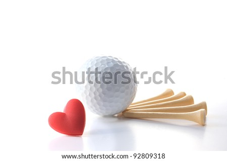 "Isolated white golf ball with wooden tees on white with red heart. Concept Father's Day theme incorporating ""I love golf"" message. Copy space. - stock photo"