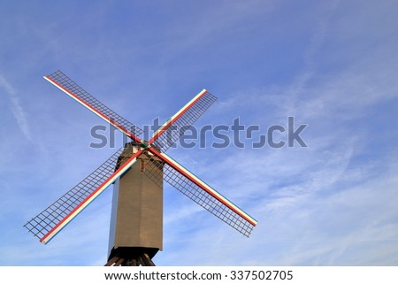 Isolated wind mill with thin clouds on blue sky in the background, Bruges, Belgium