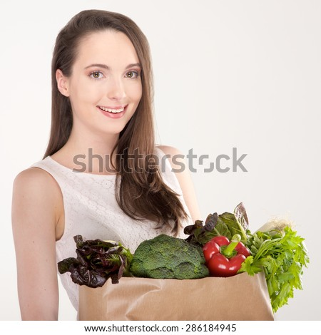 Isolated woman holding a shopping bag full of vegetables - stock photo