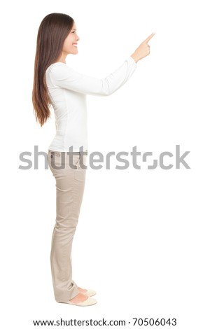 Isolated woman pointing or pushing something with index finger. Beautiful casual young woman isolated on white background in full length standing in profile. - stock photo