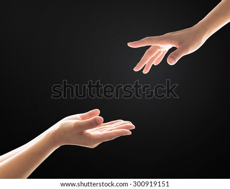 Isolated women human hands of a prayer/ receiver/ taker and a giver/ helper on black background: Charity support friendship helping and donation concept: International migrants day: World refugee day  - stock photo