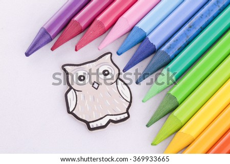 Isolated wood owl with colorful creyons - stock photo