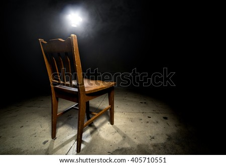 Isolated wooden chair in a dark scary prison with an interrogation spotlight - stock photo