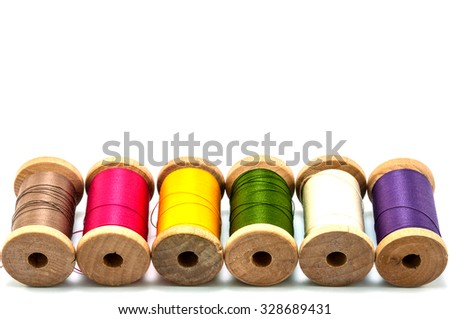 Isolated wooden spools of thread with a needle - stock photo