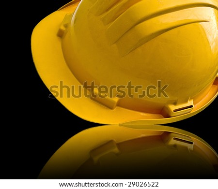 Isolated yellow helmet reflected in a black desk