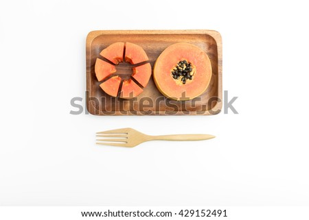 Isolated yellow ripe papaya on wood plate with fork on white background, with clipping path - stock photo