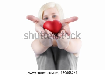 Isolated young beautiful woman presents red heart