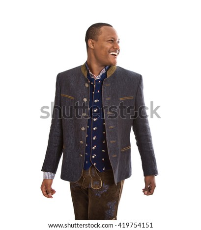 Isolated young black man wearing traditional bavarian costume looking sideways to text over white background.