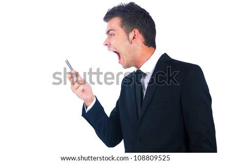 Isolated young business man screaming at phone - stock photo