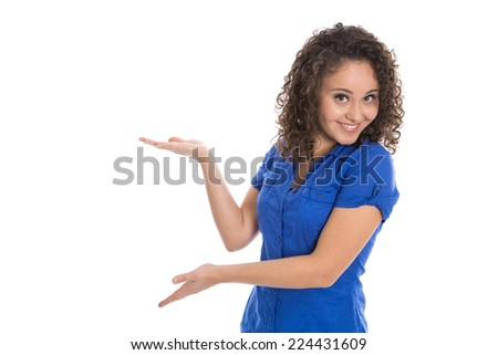 Isolated young girl presenting with hand and palm wearing blue shirt. - stock photo