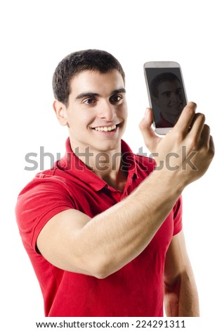 Isolated young man making selfie portrait with smart phone on white background - stock photo