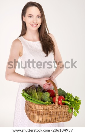 Isolated young woman holding basket of vegetables on light background - stock photo