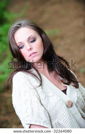 isolated young woman in a forest looking down