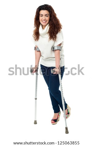 Isolation of a woman walking with help of crutches, full length portrait. - stock photo