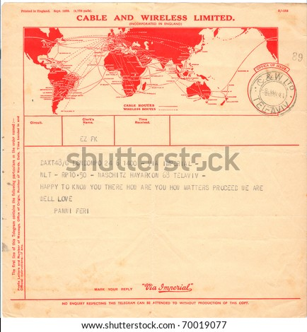 "ISRAEL - CIRCA 1941: An old used telegram form (campaign poster) sent from Tel Aviv to London showing a red map of the world with inscription ""Cable and Wireless Limited"", series, circa 1941 - stock photo"