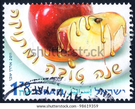 "ISRAEL - CIRCA 2011:  An used Israeli Postage stamp issued in honor of the Jewish New Year (Rosh Hashanah), showing apple soaked in honey, with inscription: ""A Happy New Year ""; series, circa 2011 - stock photo"
