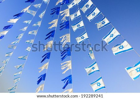Israel flags in a chain over blue sky. Independence Day. - stock photo
