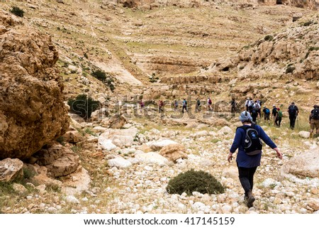 ISRAEL, NEGEV DESERT - APRIL 07, 2016: people go through rocky desert. ISRAEL, NEGEV DESERT