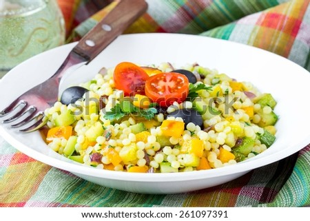 Israeli couscous ptitim with vegetables, zucchini, peppers, tomatoes, parsley, vegetarian diet healthy summer dish - stock photo