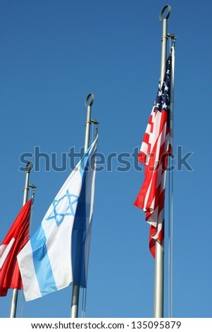 Israeli flag and American flag waving in the blue sky - stock photo