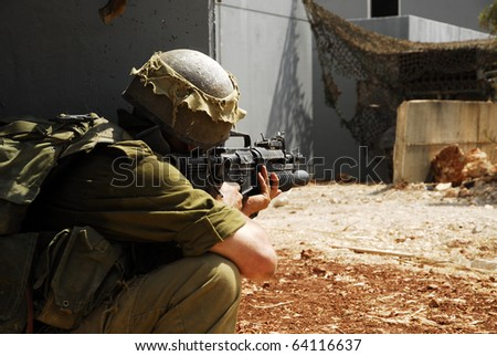 Israeli infantry soldier looking around the corner in an urban drill in the army. This is part of regular training that every soldier does. - stock photo