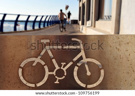 Israeli man rides a bicycle along Tel-Aviv beach on the coastline of the Mediterranean sea. Israel. - stock photo