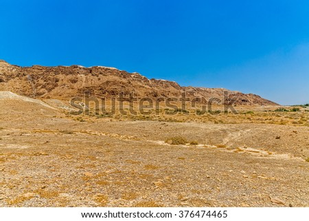 Israelis dry and sandy stone desert landscape by the Dead sea.