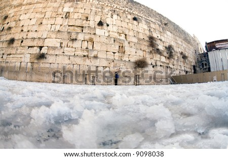 Israelite being prayed by winter in snow in western wall in Jerusalem. - stock photo