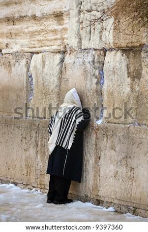 Israelite being prayed in western wall in Jerusalem in winter in snow. - stock photo