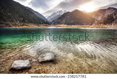 Issyk mountain lake at overcast sunset sky in Kazakhstan - stock photo